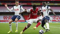 Striker Arsenal Bukayo Saka (tengah) bersaing memperebutkan bola dengan pemain Tottenham Hotspur Sergio Reguilon (kiri) dan Davinson Sanchez dalam derby London Utara Liga Inggris di Emirates Stadium, Minggu (14/3/2021). Sempat tertinggal, Arsenal menang 2-1 atas Tottenham. (Nick Potts/POOL/AFP)