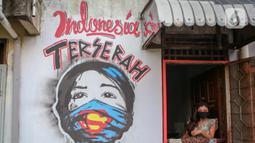 "Warga berada di dekat mural bertuliskan ""Indonesia terserah"", di Kutabumi, Tangerang, Banten, Senin (27/5/2020). Mural dibuat sebagai bentuk kritik terhadap masyarakat yang tetap beraktivitas di luar ruangan tanpa prosedur protokol kesehatan di tengah wabah COVID-19. (Liputan6.com/Angga Yuniar)"