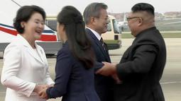 Gambar dari video yang disediakan oleh KBS, Presiden Korea Selatan, Moon Jae-in dan istrinya Kim Jung-sook disambut oleh pemimpin Korea Utara, Kim Jong-un dan sang istri, Ri Sol Ju setibanya di Pyongyang, Selasa (18/8). (Korea Broadcasting System via AP)