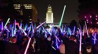 Penggemar film Star Wars berkumpul sambil membawa lightsaber (pedang sinar) saat mengikuti Glow Battle Tour di Grand Park, Los Angeles (15/12). (Photo by Chris Pizzello/Invision/AP)