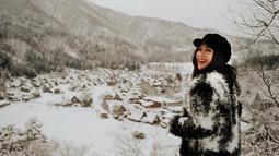 Liburan ke Jepang, gadis berusia 26 tahun ini menggunakan busana hangat serba hitam lengkap dengan topi hitam. Pemandangan perumahan berbalut salju di Shirakawa Go menjadi latar fotonya, menambah keindahan. (Liputan6.com/IG/@jscmila)