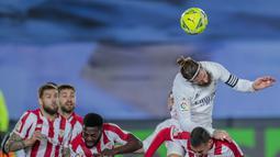 Bek Real Madrid, Sergio Ramos berusaha menyundul bola saat bertanding melawan Athletic Bilbao pada pertandingan La Liga Spanyol di di stadion Alfredo Di Stefano di Madrid, Spanyol, Rabu (16/12/2020). Madrid menang atas Bilbao 3-1. (AP Photo/Bernat Armangue)