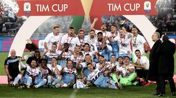 Pemain Lazio dan staf merayakan kemenangan dengan maskot mereka, burung elang dan trofi Coppa Italia pada akhir babak final yang mempertemukan Atalanta dan Lazio di Stadio Olimpico, Rabu (15/5/2019). Lazio keluar sebagai juara Coppa Italia setelah mengalahkan Atalanta 2-0. (Isabella BONOTTO/AFP)