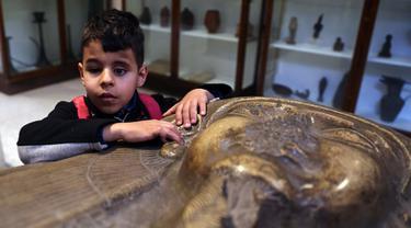 Seorang anak penyandang tunanetra menyentuh sebuah artefak di Museum Mesir di Kairo, Mesir (13/1/2020). Museum ini adalah rumah bagi koleksi antik bangsa Mesir kuno dan memiliki 120.000 koleksi. (Xinhua/Ahmed Gomaa)