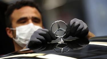 Karyawan menempelkan lambang saat merakit mobil Mercedes-Benz S-class di pabrik Mercedes, Sindelfingen, Jerman, Kamis (30/4/2020). Mulai 27 April 2020, Mercedes-Benz kembali membuka jalur produksi yang sebelumnya ditutup karena pandemi virus corona COVID-19. (AP Photo/Matthias Schrader)