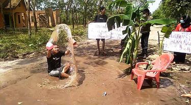 Sindir Pemerintah, Warga Ogan Ilir Mandi Air Comberan di Lubang Jalan