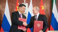 Presiden China Xi Jinping (kiri) berjabat tangan erat dengan Presiden Rusia Vladimir Putin (kanan) dalam sebuah pertemuan di Moskow (Xinhua)