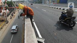 Pekerja mengecat tembok jembatan layang (flyover) simpang gaplek di Pamulang, Tangerang Selatan, Jumat (15/5/2020). Beroperasinya flyover sepanjang 446 meter yang menghubungkan Ciputat- Parung itu diharapkan membantu mengurai kemacatan yang kerap terjadi di kawasan tersebut (merdeka.com/Arie Basuki)