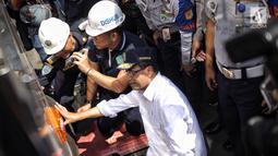 Menhub Budi Karya Sumadi mengecek ban bus penumpang saat meninjau kesiapan arus balik Lebaran di Terminal Kampung Rambutan, Jakarta, Selasa (19/6). Menurut Budi, pelaksanaan mudik di Terminal Kampung Rambutan sudah cukup baik. (Liputan6.com/Faizal Fanani)