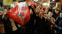 Pendukung Liverpool bernyanyi dan melambai-lambaikan bendera tim mereka di sebuah pub di alun-alun Campo de 'Fiori Roma, Italia (1/5). Liverpool akan menghadapi AS Roma di leg kedua semifinal Liga Champions. (AP Photo/Andrew Medichini )