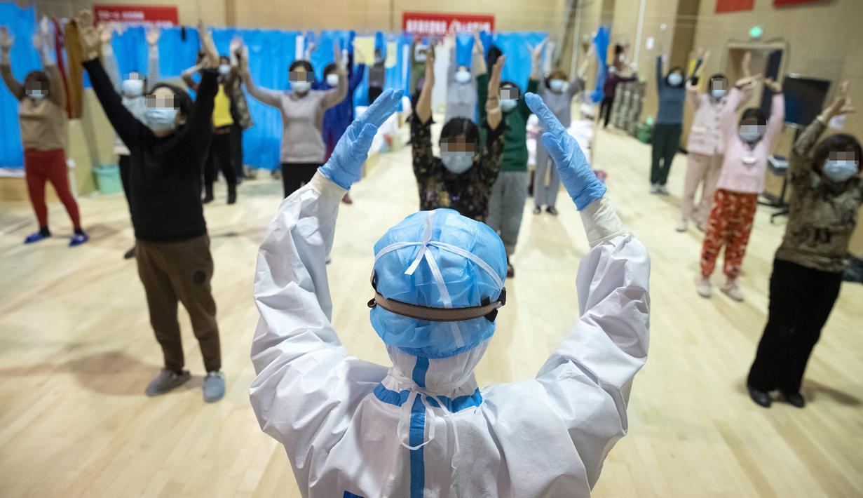 Petugas medis Yi Qin menjadi instruktur kebugaran fisik tradisional China untuk pasien COVID-19 di rumah sakit sementara di Distrik Jiangxia, Wuhan, Hubei, China (25/2/2020). Gelombang pertama sebanyak 23 pasien diizinkan pulang setelah menggunakan pengobatan tradisional China. (Xinhua/Shen Bohan)