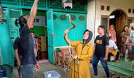Iin Ayu (55) bermain dengan ular kobra di halaman rumahnya di Kelurahan Karangpucung, Purwokerto Selatan, Kabupaten Banyumas, Rabu (17/12) (Liputan6.com/Rudal Afgani Dirgantara)