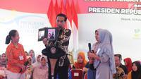 Presiden Joko Widodo atau Jokowi menunjukkan foto saat menyalurkan bantuan sosial Program Keluarga Harapan (PKH) dan Bantuan Pangan Non Tunai (BPNT) kepada seribu warga Depok, Jawa Barat, Selasa (12/2). (Liputan6.com/Herman Zakharia)