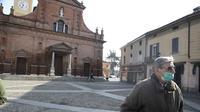 Seorang pria mengenakan masker berjalan di depan gereja San Biagio, Codogno, dekat Lodi, Italia Utara  (22/2/2020). Pihak berwenang Italia memerintahkan penutupan sekolah, bar, dan ruang publik lainnya di 12 kota, menyusul banyaknya kasus virus corona baru muncul di negara itu. (AP Photo/Luca Bruno)