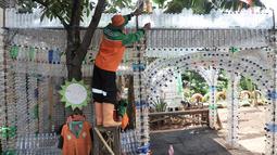 Petugas UPK Badan Air DLH DKI Jakarta saat merapikan instalasi botol yang menghiasi pos di Pasar Rebo, Jakarta, Selasa (12/3). Lebih dari seribu botol plastik bekas dipasang untuk menghiasi Pos  UPK Badan Air di Pasar Rebo. (merdeka.com/Iqbal Nugroho)