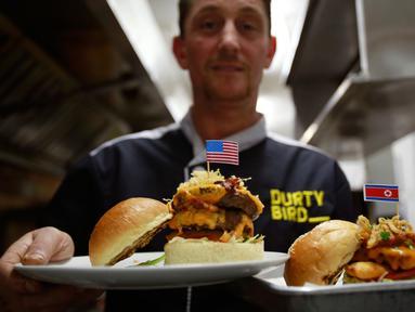 """Pemilik restoran, Collin Kelly memperlihatkan burger """"Durty Donald"""" dan """"Kim Jong Yum""""  yang baru dibuat di Hanoi, Vietnam, 24 Februari 2019. Restoran ini membuat 2 jenis burger khusus untuk menyambut kedatangan Kim Jong-un dan Donald Trump. (AP/Hau Dinh)"""