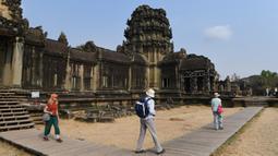 Sejumlah wisatawan berjalan di Candi Angkor Wat, Provinsi Siem Reap, Kamboja, Kamis (5/3/2020). Menurut World Travel and Tourism Council, wabah virus corona (COVID-19) membuat sektor pariwisata dunia kehilangan USD 22 miliar. (TANG CHHIN Sothy/AFP)