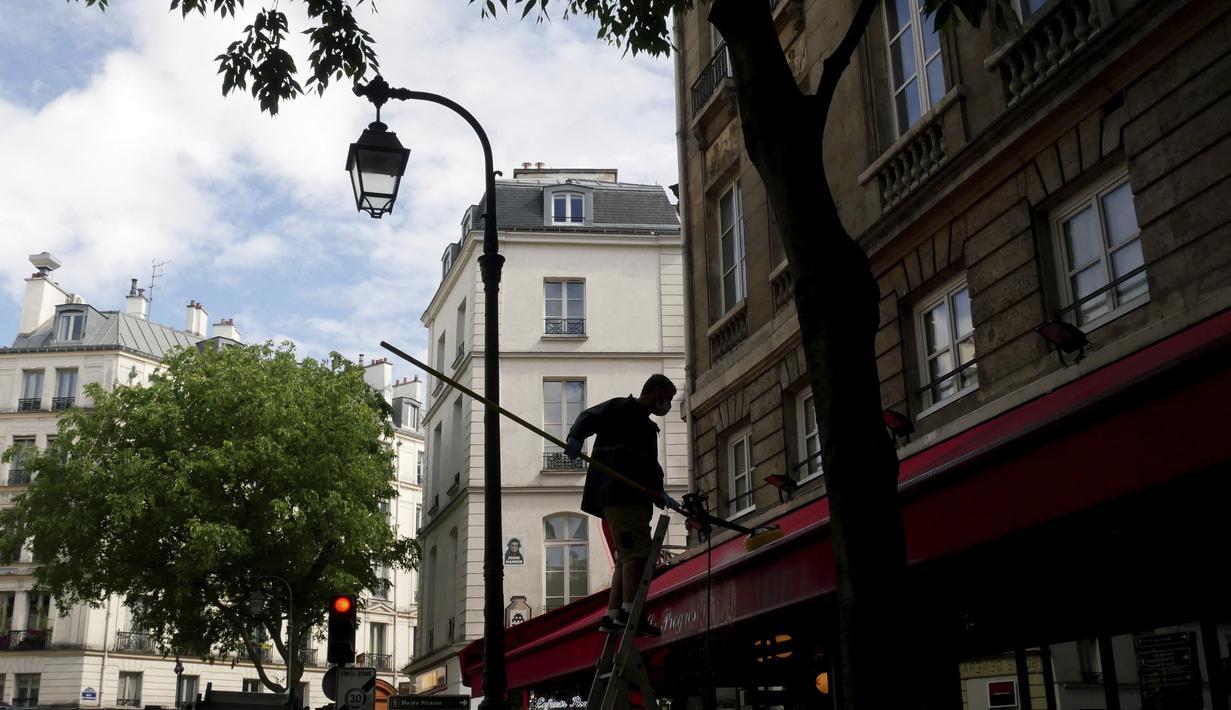 Seorang pekerja membersihkan tenda sebuah restoran, di Paris, Senin (17/5/2021). Teras luar kafe dan restoran Prancis akan diizinkan untuk dibuka kembali pada 19 Mei bersama dengan museum, bioskop, teater, dan ruang konser dalam kondisi tertentu. (AP Photo/Thibault Camus)