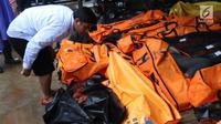 Warga melihat jenazah korban gelombang Tsunami Anyer di Puskesmas Carita, Banten, Minggu (23/12). Tim SAR masih melakukan pencarian jenazah yang sebagian besar berasal dari Pantai Carita. (Liputan6.com/Angga Yuniar)