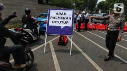 Polisi mengarahkan pengendara sepeda motor yang melintas di sekitar Gedung DPR RI, Jakarta, Kamis (17/10/2019). Polisi kembali menutup sejumlah ruas jalan menuju kawasan Gedung DPR RI guna menjaga kondusifitas jelang pelantikan Presiden dan Wakil Presiden terpilih. (Liputan6.com/JohanTallo)