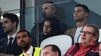 Pemain Juventus, Cristiano Ronaldo dan kekasihnya, Georgina menyaksikan timnya menghadapi Young Boys pada laga kedua Grup H Liga Champions di Allianz Stadium, Selasa (2/10). Ronaldo hanya menjadi penonton karena terkena kartu merah. (AFP/Marco BERTORELLO)