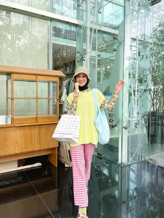 Referensi outfit buat piknik, padukan vest polos warna kuning dengan inner motif floral dan plaid pants warna kontras. Bucket hat sebagai aksesori bisa bikin lookmu makin catchy! (Instagram/tantrinamirah).
