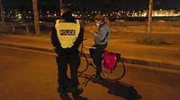 Polisi memeriksa seorang wanita yang mengendarai sepeda selama jam malam dekat Majelis Nasional di Paris, Perancis, Selasa (15/12/2020). Pelanggar jam malam akan dikenakan denda 135 Euro atau sekitar Rp 2,3 juta. (AP Photo/Francois Mori)