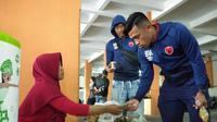 Pemain PSM Makassar, Benny Wahyudi (kanan), saat membeli makanan sebelum menghadapi PSIS Semarang di Stadion Moch Soebroto, Magelang, Sabtu (16/3/2019). (Bola.com/Vincentius Atmaja)
