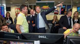 Pangeran Harry bereaksi sambil mengangkat telepon saat menjadi broker dalam acara amal tahunan ICAP di London, Rabu (7/12). Pangeran Harry menjadi broker dadakan untuk mengumpulkan dana amal dari 60 kantor di seluruh dunia. (REUTERS/Geoff Pugh/Pool)