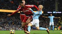 Pemain Watford, Kiko Femenia (kiri) berusaha menahan laju pemain Manchester City, David Silva saat berebut bola pada lanjutan Premier League di Etihad stadium, Manchester, (2/1/2018).  City menang 3-1. (AFP/ Oli Scarff)