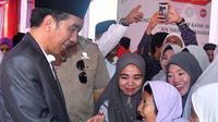 Presiden Joko Widodo atau Jokowi menyapa warga saat meresmikan Bank Wakaf Mikro di Serang, Banten, Rabu (14/3). Tiap kelompok nasabah Bank Wakaf Mikro terdiri dari tiga hingga lima orang. (Liputan6.com/Pool/Biro Setpres)