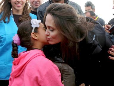 Utusan khusus lembaga pengungsi PBB, aktris Angelina Jolie mendapat ciuman seorang anak Suriah saat berkunjung ke Kamp Pengungsi Zaatari di Mafraq, Yordania, Minggu (28/1). Jolie mengaku prihatin dengan kondisi pengungsi Suriah. (AP Photo/Raad Adayleh)
