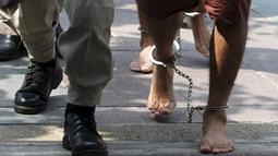 Kaki dua tersangka pemboman Yusufu Mieraili dan Bilal Mohammed yang diborgol saat berjalan ke Pengadilan Militer (20/4). Yusufu dan Bilal didakwa terkait pemboman sebuah kuil di Bangkok yang terjadi pada 17 Agustus 2015 lalu. (REUTERS/Chaiwat Subprasom)