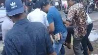 Warga Pati bersama polisi mengikat pasangan pria telanjang yang diduga over dosis sabu. (foto: Liputan6.com/istimewa/felek wahyu)