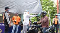 Upaya menghambat penyebaran Covid-19, tenaga medis memeriksa suhu tubuh warga yang akan masuk ke Kota Manado.