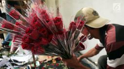 Pedagang menata bunga mawar di Rawa Belong, Jakarta (13/2). Keuntungan dari hari biasa memang didapatkan pedagang karena banyaknya masyarakat membeli bunga mawar khusus dibagikan kepada keluarga atau seseorang yang disayangi. (Liputan6.com/Johan Tallo)