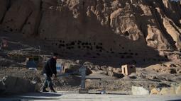Seorang polisi Hazara mengumpulkan air dari pompa tangan dekat situs patung Buddha raksasa yang dihancurkan oleh Taliban pada 2001 di Provinsi Bamiyan, Afghanistan, 3 Maret 2021. Dua patung Buddha raksasa ini pernah dihancurkan oleh Taliban karena dianggap tidak Islami. (WAKIL KOHSAR/AFP)