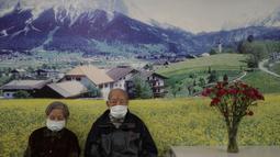 Pasangan lanjut usia yang mengenakan masker pelindung duduk di sebuah panti jompo pada Hari Valentine di Hong Kong, Jumat, (14/2/2020). (AP Photo/Kin Cheung)