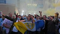 Pendukung Leeds United berkumpul di luar Elland Road merayakan kembalinya klub ke Liga Premier  di Leeds, Inggris (17/7/2020). Leeds berhasil menyegel satu tiket promosi setelah salah satu rivalnya di divisi Championship, West Bromwich Albion kalah 1-2 di kandang Huddersfield Town. (AFP/Paul Ellis)