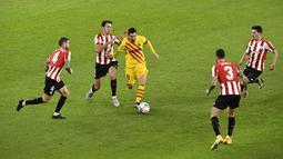 Pemain Barcelona Lionel Messi (tengah) menggiring bola melewati empat pemain Athletic Bilbao pada pertandingan Liga Spanyol di Stadion San Mames, Bilbao, Spanyol, Rabu (6/1/2021).Barcelona menang 3-2 dengan dua gol dari Lionel Messi. (AP Photo/Alvaro Barrientos)