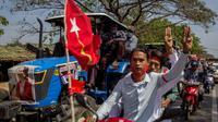 Para pengunjuk rasa dengan skuter dan petani yang mengendarai traktor dengan poster pemimpin sipil Myanmar Aung San Suu Kyi yang ditahan di bagian depan mengambil bagian dalam demonstrasi menentang kudeta militer di Thongwa, di pinggiran Yangon (12/2/2021). (AFP/STR)
