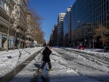 Seorang perempuan berjalan melewati salju di Madrid, Spanyol, Senin (11/1/2021). Ibu kota Spanyol itu berusaha bangkit kembali setelah menghadapi badai salju terburuk dalam 50 tahun terakhir yang melumpuhkan sebagian besar wilayah Spanyol tengah selama akhir pekan. (AP Photo/Manu Fernandez)