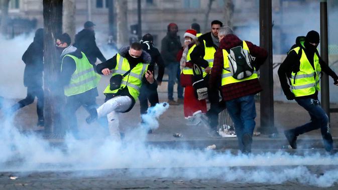 Demonstran menendang tabung gas air mata saat kerusuhan menentang kenaikan harga bahan bakar di Paris, Prancis, Sabtu (24/11). Polisi menggunakan gas air mata dan meriam air untuk membubarkan demonstran. (AP Photo/Christophe Ena)