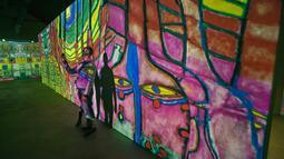 Pengunjung berswafoto dengan karya seniman Austria, Friendensreich Hundertwasser dalam pameran seni proyeksi di galeri l'Atelier des Lumieres di Paris, Prancis (24/4). (AP/Michel Euler)