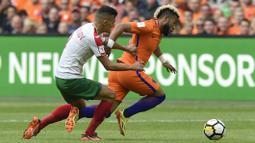 Pemain Belanda, Tonny Vilhena (kanan) melewati adangan pemain Bulgaria, Georgi Kostadinov pada laga grup A kualifikasi Piala Dunia 2018 di Amsterdam, (3/9/2017). Belanda menang 3-1. (AFP/John Thys)