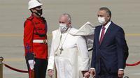 Paus Fransiskus disambut oleh PM Irak Mustafa al-Kadhimi saat tiba di Bandara Internasional Baghdad, Irak, Jumat (5/3/2021). Paus Fransiskus datang ke Irak untuk mendesak umat Kristen tetap tinggal dan membantu membangun kembali Irak setelah bertahun-tahun perang. (AP Photo/Andrew Medichini)