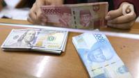 Petugas menunjukkan mata uang rupiah dan dolar di Jakarta, Senin (9/11/2020). Menjelang siang, rupiah terus menguat ke level 14.145 per dolar AS. (Liputan6.com/Angga Yuniar)