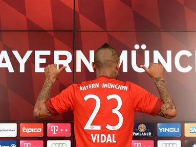 Pemain baru Bayern Munchen Arturo Vidal menunjukan kostum tim barunya dengan nomor punggung 23 saat jumpa pers di Munich, Jerman, Selasa (28/7/2015). (AFP Photo/Christof Stache)
