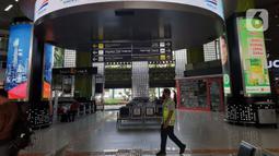 Petugas melintasi ruang tunggu keberangkatan Stasiun Gambir, Jakarta, Jumat (27/3/2020). PT Kereta Api Indonesia (Persero) membatalkan sejumlah jadwal perjalanan menyusul meluasnya penyebaran virus corona, pembatalan itu dilakukan mulai 26 Maret 2020. (Liputan6.com/Helmi Fithriansyah)
