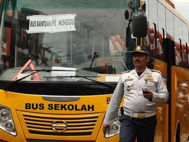 Petugas mengawal bus sekolah untuk mengangkut penumpang di Terminal Blok M Jakarta, Senin (21/12/2015). Bus sekolah dikerahkan untuk mengantisipasi penumpukan penumpang seiring mogoknya sejumlah sopir metromini. (Liputan6.com/Helmi Fithriansyah)